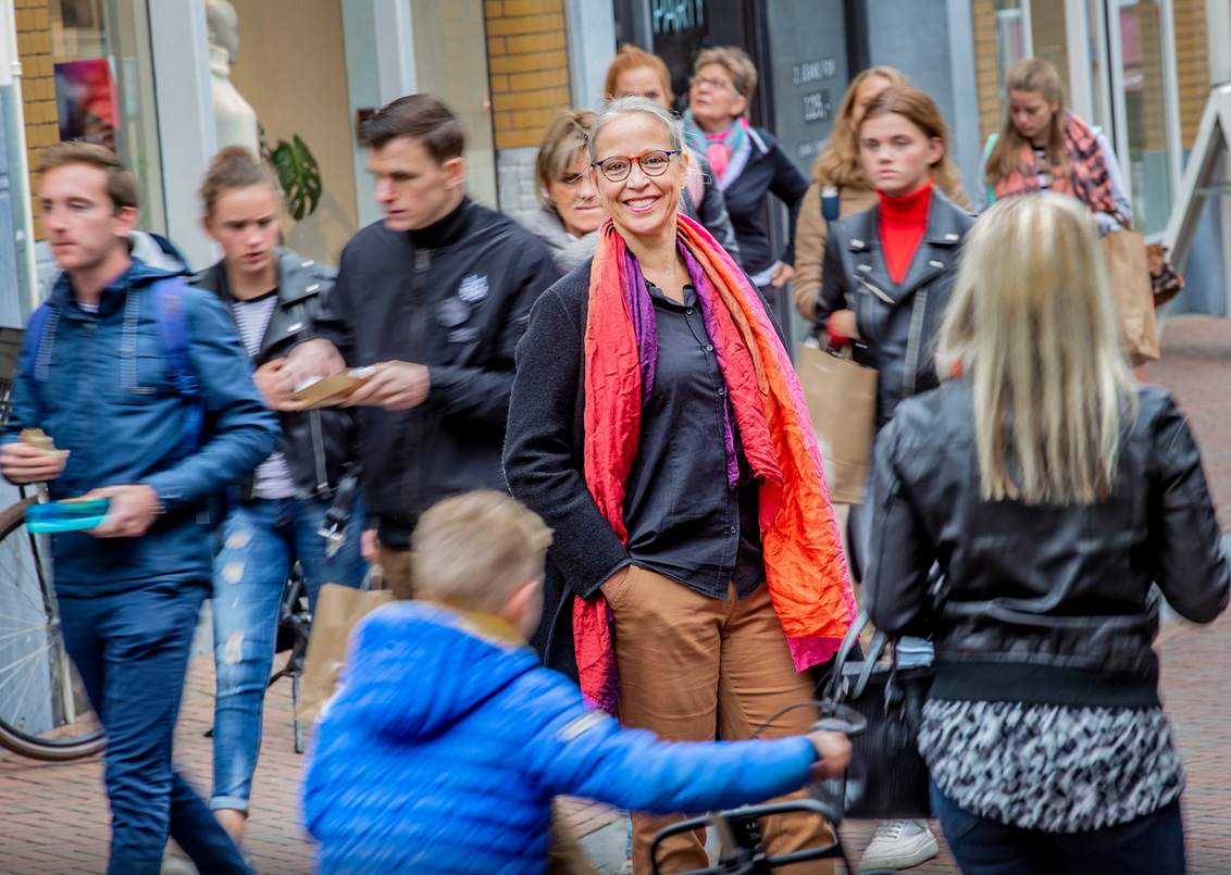 Foto: Rob Voss (2019) Nicolet Theunissen tussen de mensen in de Apeldoornse Hoofdstraat. https://www.destentor.nl/apeldoorn/nicolet-theunissen-uit-apeldoorn-zet-alles-op-wereldwijde-verdubbeling-van-positief-gedrag~af370a6d/